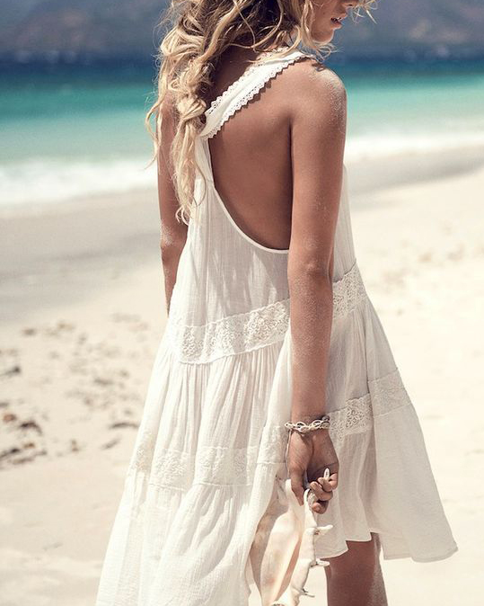 Woman on beach in white dress with bracelet