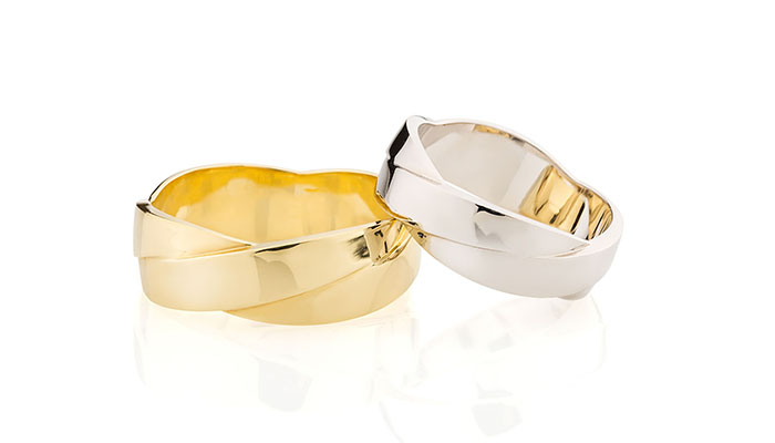 Casual style silver and golden ring isolated on white background. Wedding rings band twisted design