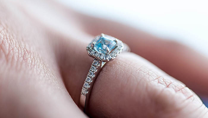 Engagement ring with blue center stone, on finger