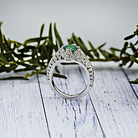 Platinum Fashion ring features Round cut Green Emerald and 0.80ct TCW Diamonds